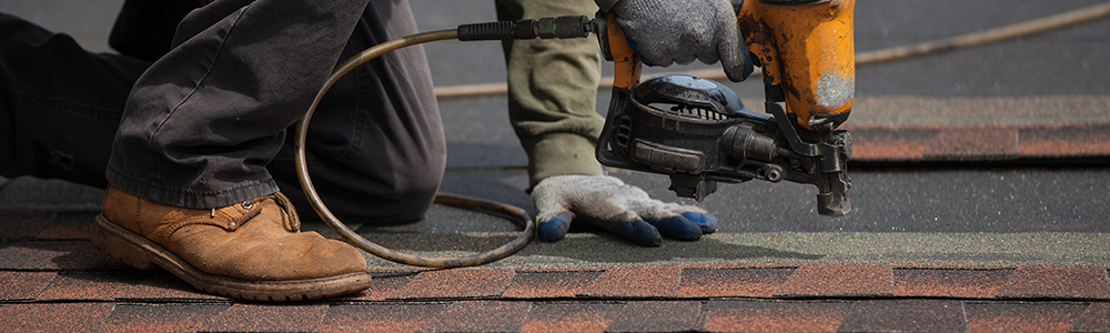 worker nailing roofing material photo